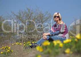 Young beautiful woman sitting in blooming garden