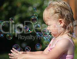 Happy little girl playing with soap bubbles int he garden