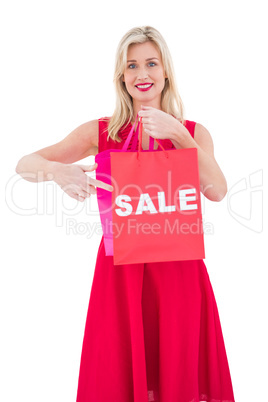 Stylish blonde in red dress showing sale bag