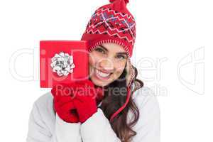 Festive brunette in winter clothes showing red gift