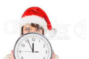Festive brunette holding a clock