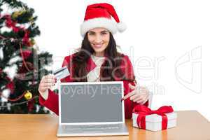 Festive brunette shopping online with laptop and pointing screen