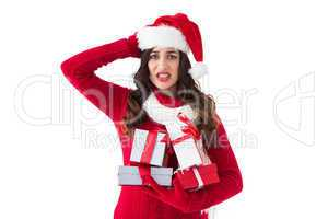 Stressed brunette in santa hat holding gifts