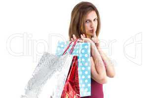 Pretty woman holding shopping bags with finger to her lips