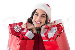 Excited brunette holding shopping bags full of gifts