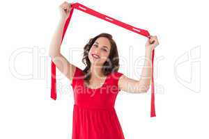 Stylish brunette in red dress holding scarf