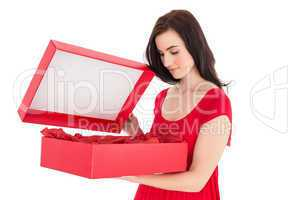 Stylish brunette in red dress opening gift