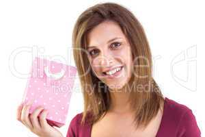 Young woman holding a pink gift bag smiling at camera