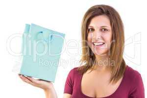 Brunette holding a gift bag smiling at camera