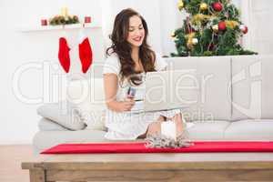 Pretty brunette shopping online with laptop at chistmas