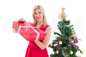 Festive blonde in red dress holding gift