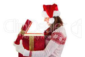 Smiling brunette in warm clothing opening a gift