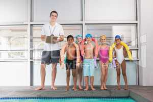 Swimming coach with his students poolside
