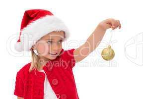 Cute little girl wearing santa hat holding bauble