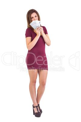 Festive brunette holding fan of euros