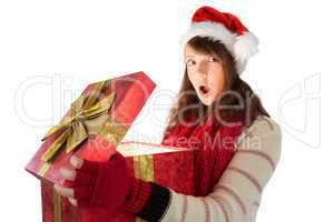 Young woman opening a glowing christmas gift