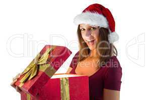 Pretty brunette in santa hat opening a gift smiling at camera