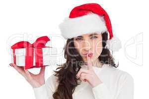 Festive brunette holding gift and keeping a secret