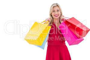 Stylish blonde in red dress holding shopping bags