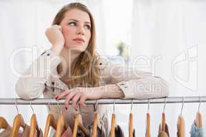 Pretty blonde thinking through clothes rail