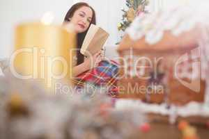 Cheerful brunette reading on the couch with cover at christmas