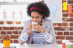 Interior designer drinking coffee at desk