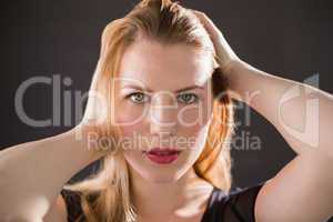 Pretty blonde model in black dress posing hands in the hair