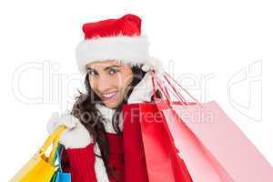 Festive brunette in winter wear holding shopping bags