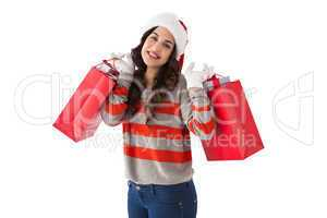 Cheerful brunette holding shopping bags full of gifts