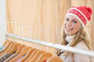 Pretty blonde smiling at camera by clothes rail