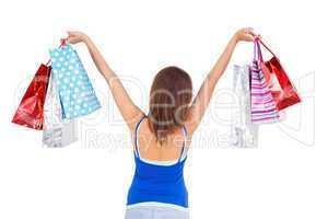 Rear view of a brunette woman raising shopping bags