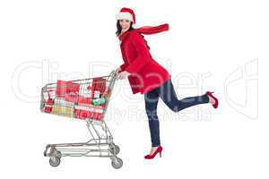 Festive brunette pushing trolley full of gifts