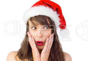 Festive brunette looking surprised with hands on face