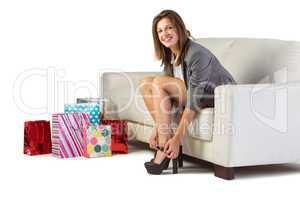 Well dressed woman sitting on couch taking off her shoes