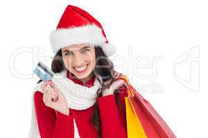 Excited brunette holding shopping bags and credit card