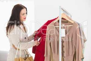 Pretty brunette choosing red jacket
