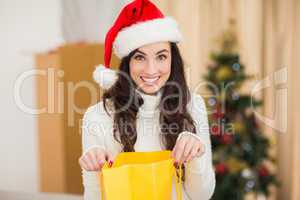Festive brunette opening gift bag