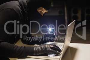 Robber hacking a laptop while making light with his phone