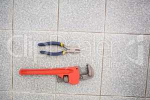 Wrench and pliers on bathroom floor