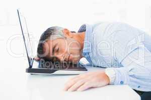 Man with grey hair sleeping on his laptop