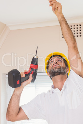 Construction worker drilling hole in ceiling