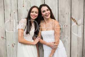 Pretty friends smiling in white dresses