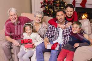 Multi generation family holding gifts on sofa