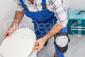 Plumber installing lid on toilet