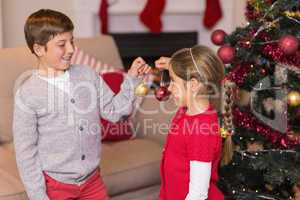 Brother and sister decorating the christmas tree with baubles