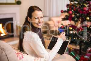 Smiling brunette shopping online with laptop at christmas