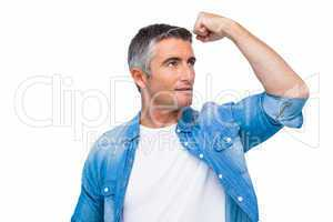 Man with grey hair tensing arm muscle