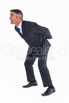 Businessman bending with arms on his back