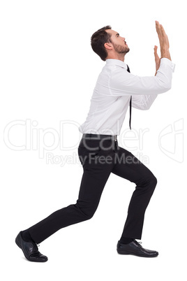 Businessman standing with bent legs and pushing