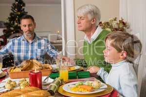 Extended family saying grace before christmas dinne